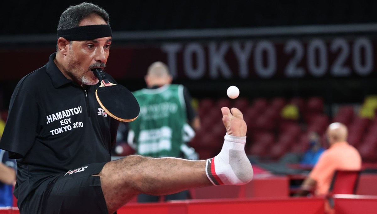 Ibrahim Hamadtou raketi ağzıyla tutuyor, servis atarken ayağını kullanıyor (Tokyo Paralimpik Oyunları)
