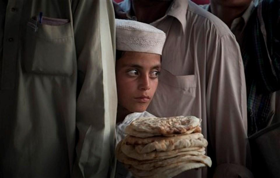 Svat Vadisi'nde kaşan Pakistanlı bir çocuk, Lahor'daki mülteci kampında yemek sırası beklerken.