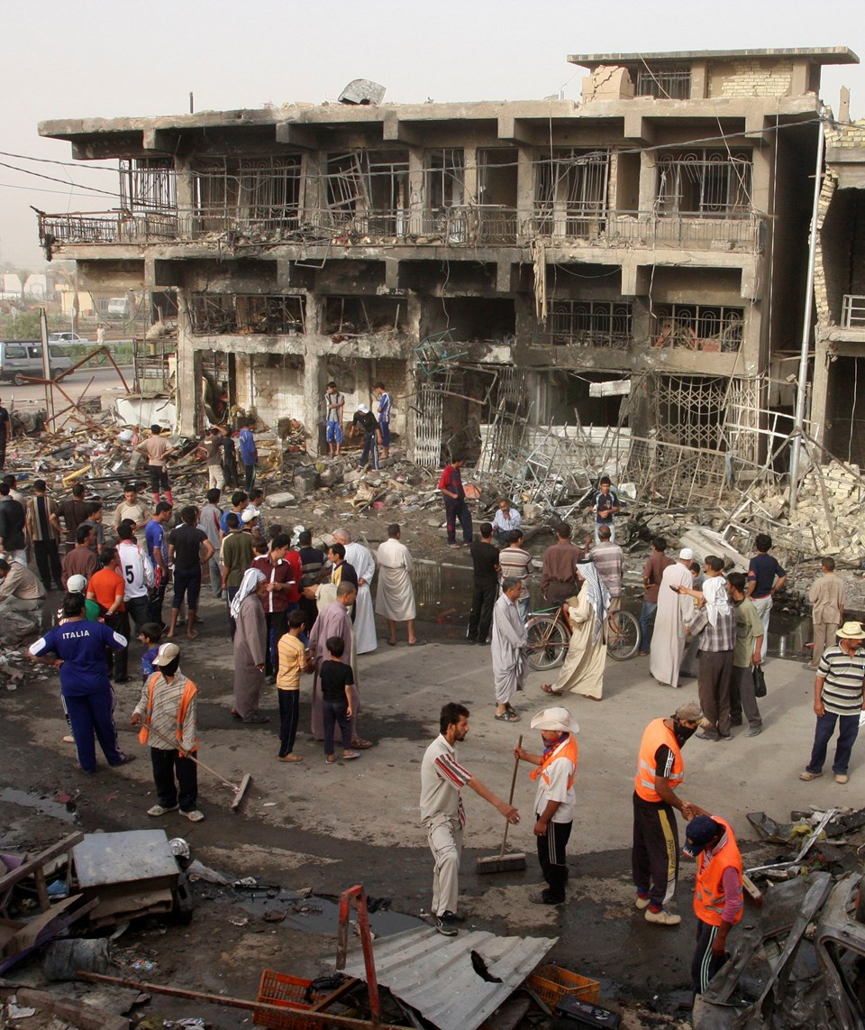 Residents gather at the site of a bomb attack in Baghdad's Shula district May 21, 2009. A parked car bomb ripped through the poor mostly Shi'ite district of Shula in northwest Baghdad on Wednesday, killing 35 people and wounding 72 others near a popular r
