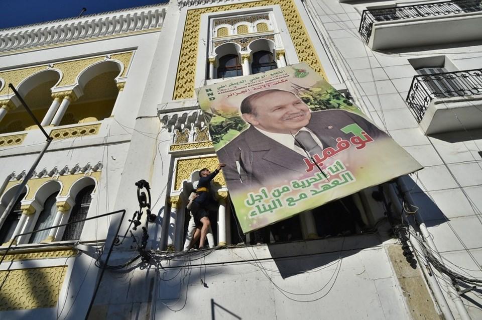 22 Şubat 2019'da çekilen bu fotoğrafta Cezayirli göstericiler, Cumhurbaşkanı Abdülaziz Buteflika'nın resminin bulunduğu büyük bir reklam panosunu yırtıyor