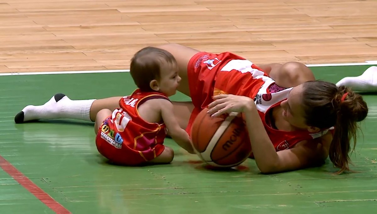 Basketball mother breastfeeding her daughter between the halves