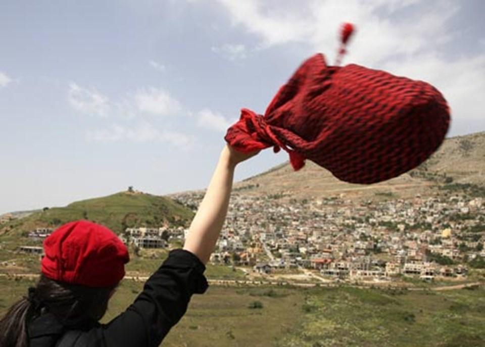 Sınırın Suriye tarafından bir kız, Majdel Şems'e el sallıyor.