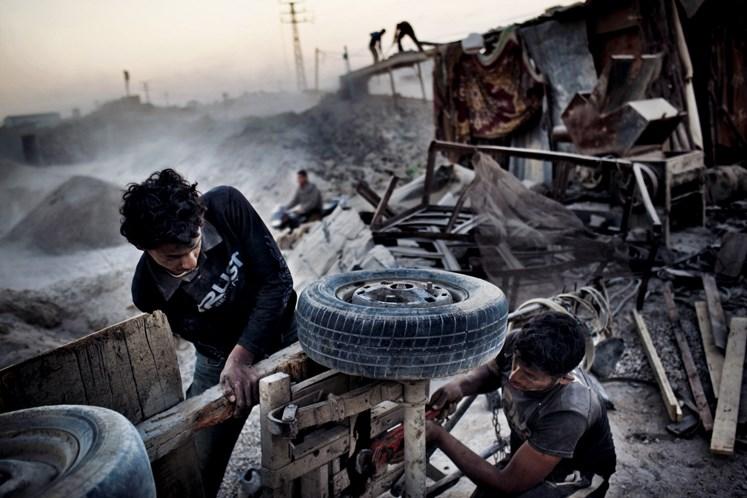 Gazzeliler 2008–2009 tarihli Dökme Kurşun Harekâtı'ndan kalma dağ gibi molozları toplamak için bir eşek arabasını tamir ediyor. Bu moloz geridönüşümle inşaatlarda kullanılıyor.