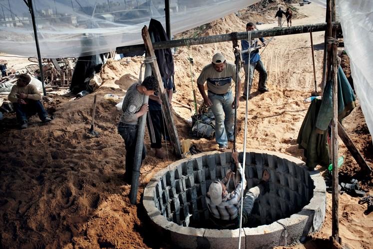 Yenİ bir tünel sahibi (beyaz kepli), kazıya devam etmek için kuyu bacasından inen oğlunu izliyor. Zengin tünel sahiplerinin gücü mekanik vinçlere yetiyor, ama tünel ticaretinden pay alabilmek için yıllarca para biriktiren bu adamın tek seçeneği ailesi ve