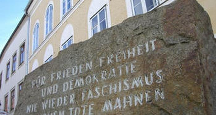 """Hitler'in doğduğu evin önünde Mathausen Toplama Kampı'ndan getirtilen büyük bir granit taş bulunuyor. Taşın üzerinde """"Barış, Özgürlük ve Demokrasi için. Faşizme bir daha asla. Milyonlarca ölü uyarıyor"""" yazıyor."""