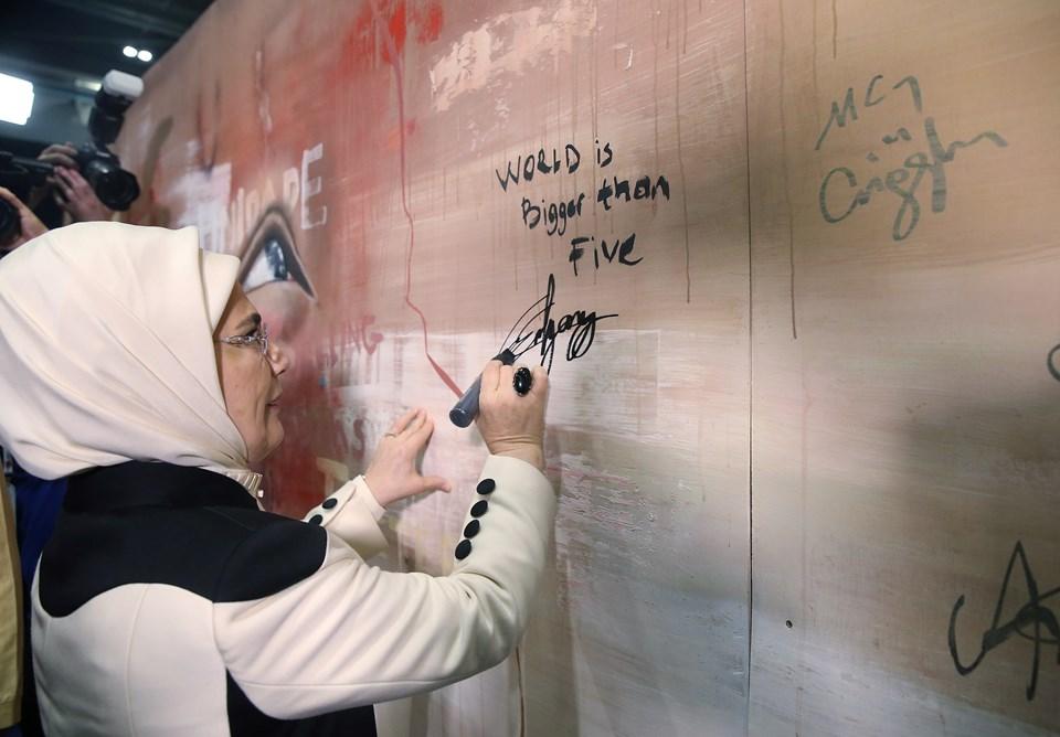 """Emine Erdoğan,: Londra ziyaretimde, insanlık dramlarını resmederek dünyaya duyuran İngiliz ressam Jonathan Darby ile biraraya geldim. İmza teklifi ile """"Dünya beşten büyüktür"""" mesajını onun sanat eseriyle ölümsüzleştirmekten memnuniyet duydum."""