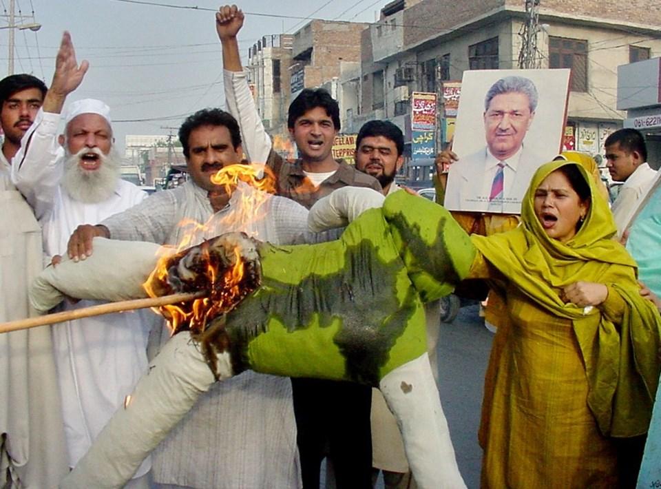 Ev hapsinde tutulduğu sırada aktivistlerAbdul Kadşr Han'ın bir fotoğrafını tutarken Başbakan Pervez Müşerref'in büstünü yakıyorlar.