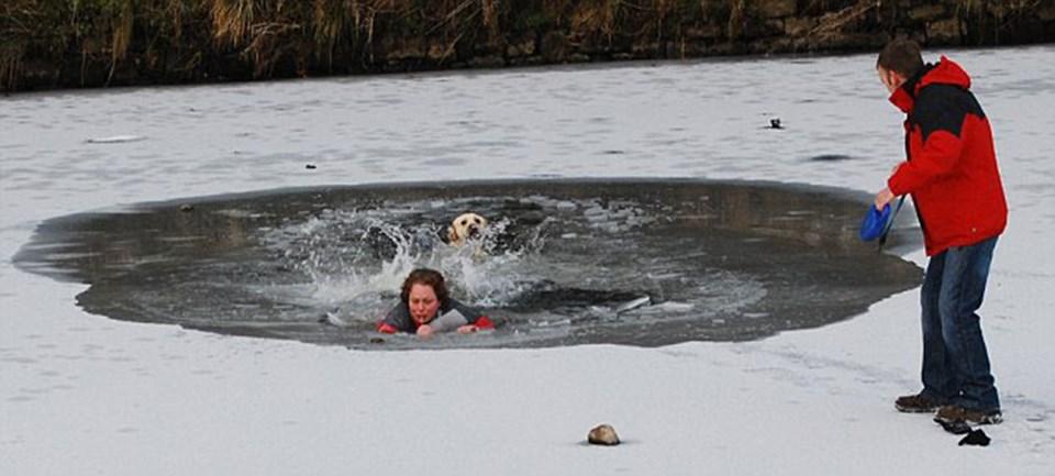 Kırılan buz ile köpek sahibi de donmuş nehirin içine düşüyor