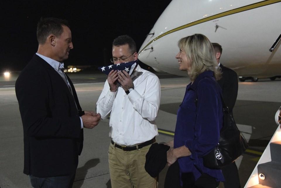 Rahip Brunson, Almanya'da ABD Büyükelçisi'nin sunduğu bayrağı öptü.