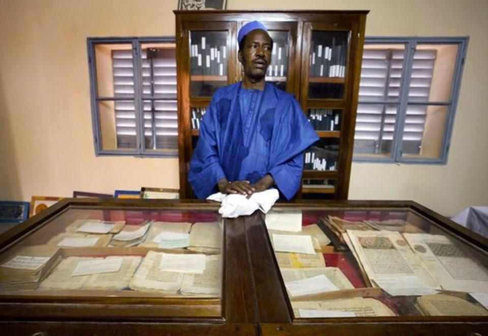 2004 yılında Ahmed Baba Enstitüsü'nde çekilen fotoğrafta antik el yazmalarıyla ilgilenen bir çalışan görülüyor.