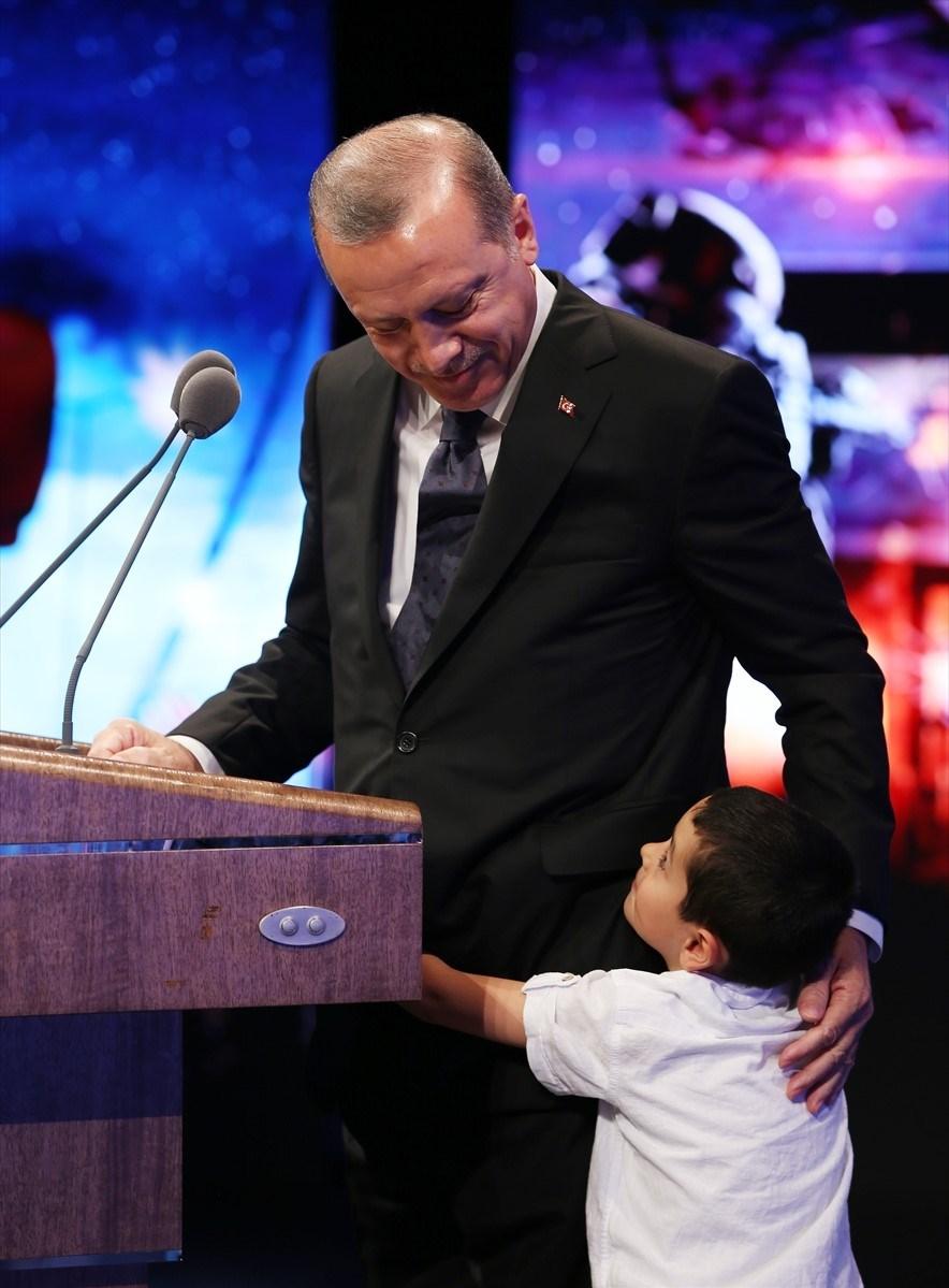 Cumhurbaşkanı Erdoğan, konuşması esnasında yanına gelen şehit çocuğu ile yakından ilgilendi.