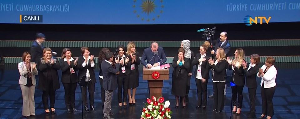 """Cumhurbaşkanı Erdoğan, konuşmasının sonunda, """"güzellik uzmanlarının tıbbi cihaz kapsamına girmeyen cihaları kullanarak tıbbi amaçlı olmayan işlemleri yapabilmesi ve bu uzmanların sahip olması gereken belgeleri düzenleyen Bakanlar Kurulu kararını"""" imzaldı. O esnada meslek temsilcileri de sahnedeydi."""